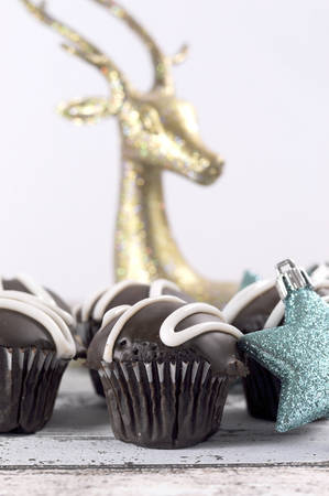 Festive chocolate cupcakes on blue and white shabby chic table with blue glitter stars and reindeer Christmas ornaments. photo