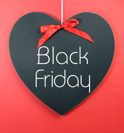 long weekend: Black Friday shopping sale concept with message on a heart shape blackboard against a red .