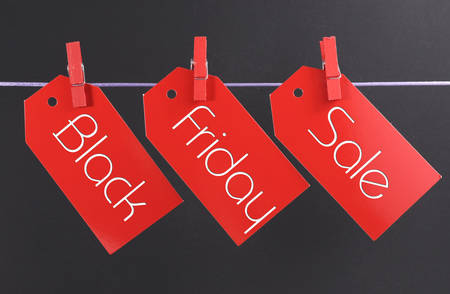 Black Friday shopping sale concept with message written across red ticket sale tags hanging from pegs on a line