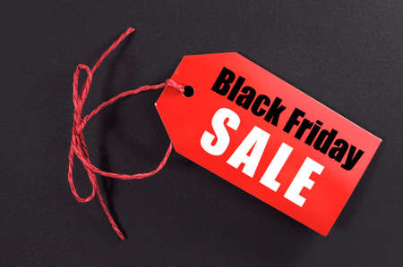 Black Friday shopping sale concept with red tiket Sale tag close up on black .