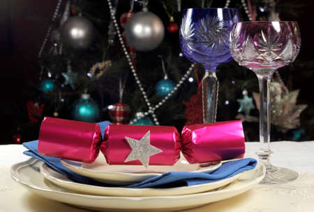 Beautiful Christmas table setting in front of Christmas Tree, with pink and blue long stem crystal wine glasses and decorations photo