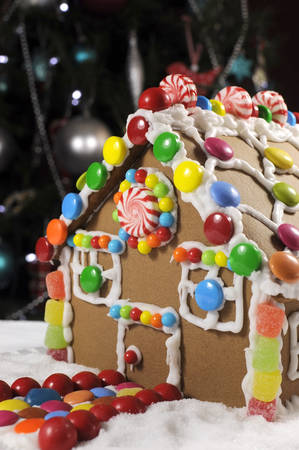casita de dulces: Hermosa mesa de Navidad poniendo en frente de árbol de Navidad, con una casa de pan de jengibre hecha con escarcha y dulces dulces