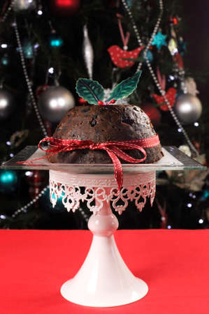 plum pudding: Impostazione di fronte albero di Natale, con un classico plum pudding con agrifoglio sulla tovaglia rosso Bella tavola di Natale