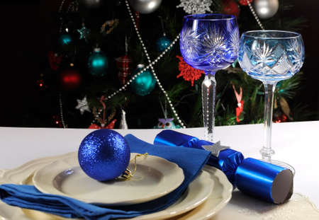 Beautiful Christmas table setting in front of Christmas Tree, with blue theme crystal wine goblet glasses  photo