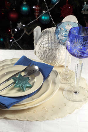 Beautiful Christmas table setting in front of Christmas Tree, with blue theme crystal wine goblet glasses and turkey tureen  photo