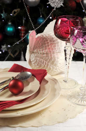 Beautiful Christmas table setting in front of Christmas Tree, with red crystal wine goblet glasses and turkey tureen  photo