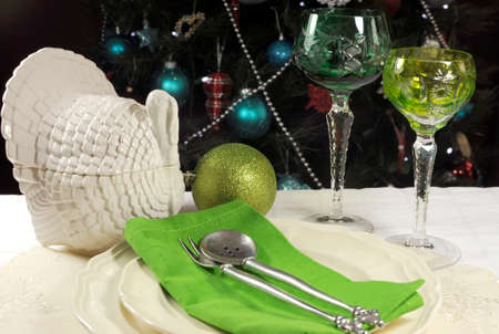 Beautiful Christmas table setting in front of Christmas Tree, with green crystal wine goblet glasses and turkey tureen  photo