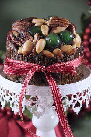 glace: Festive Christmas food, fruit cake with glace cherries and nuts on white cake stand with holiday berry wreath in green background  Selective focus  Close up vertical