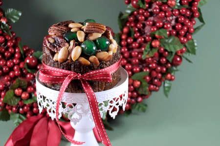 plum pudding: Cibo Festa di Natale, torta di frutta con ciliegie candite e noci su bianco Torta stand con bacche vacanza corona in sfondo verde Messa a fuoco selettiva