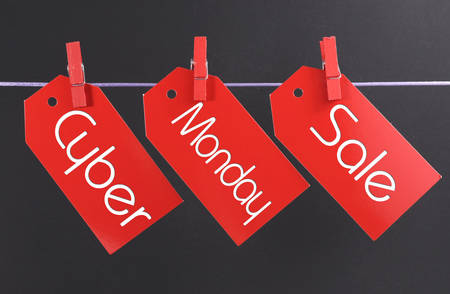 Cyber Monday online Christmas shopping sale concept with text across three red tickets hanging from pegs on a line Stock Photo
