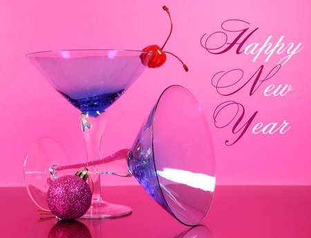 Pink theme Happy New Year party with vintage blue martini cocktail glass and New Years eve decorations against a pink background, with greeting text