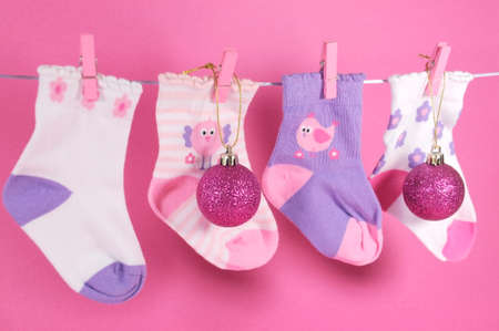 childrens food: Festive childrens baby stockings hanging from pegs on a line with Merry Christmas ornaments and decorations against a pretty pink .
