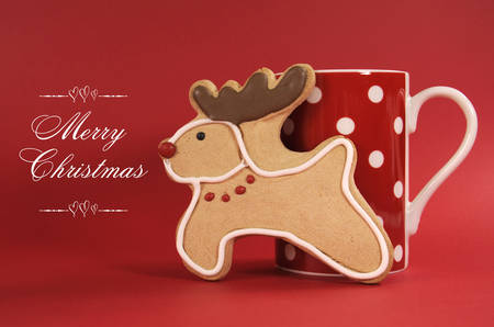 Reindeer vanilla cookie biscuit with red polka dot cup of coffee against a festive red background for happy holidays or merry Christmas cheer  photo