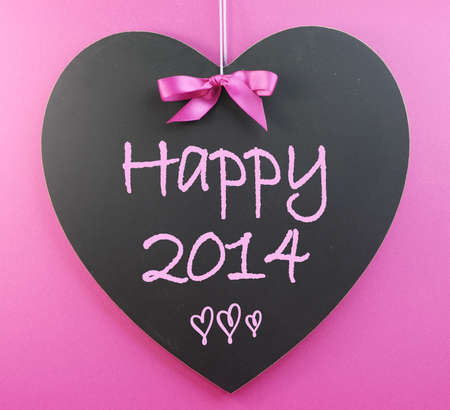 Happy New Year 2014 message greeting written on heart shape blackboard against a pink. Stock Photo