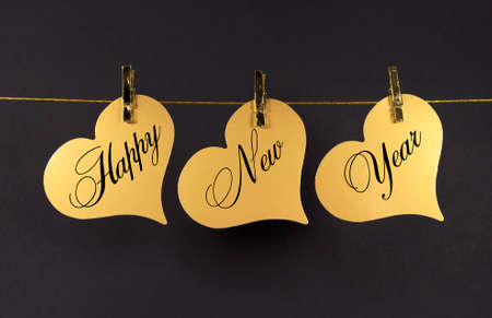 Happy New Year message greeting text on gold hearts hanging from pegs on a line against a black photo