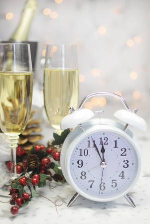Happy New Year table setting with white retro clock showing five to midnight with champagne and festive decorations against white starry with bokeh lights. photo