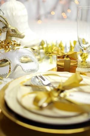 White and gold Happy New Year elegant fine dining table place setting in gold theme Christmas and New Year decorations. photo