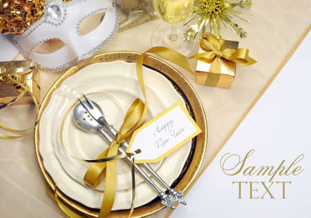 White and gold Happy New Year elegant fine dining table place setting in gold theme Christmas and New Year decorations.
