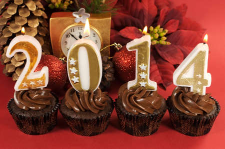 Happy New Year chocolate cupcakes with 2014 number candles against red festive. Stock Photo - 24500563