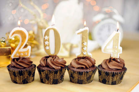 Happy New Year chocolate cupcakes with 2014 candles against bokeh Christmas lights
