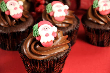 Christmas chocolate cupcakes with Santa faces against a red festive. photo
