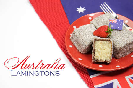 australian flag: Australia Day, Anzac Day or Australian public holiday or national event dining table place setting with polka dot china and Australian flag, in red, white and blue theme colors, with a plate full of lamingtons and copy space for your text here. Stock Photo