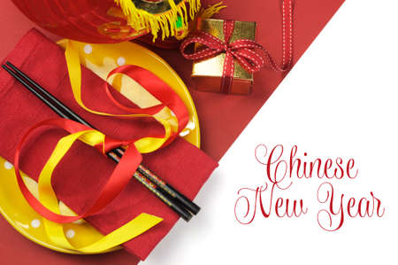 message text: Happy Chinese New Year dining table place setting with red and gold decorations and chopsticks with greeting message text. Stock Photo