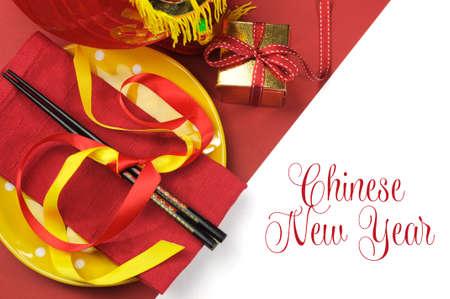 Frohes neues Jahr Esstisch Gedeck mit Rot-und Goldschmuck und Stäbchen mit Grußnachrichtentext ein.