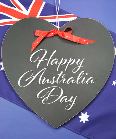 Happy Australia Day greeting written on heart shape blackboard against Australian Flag background. photo