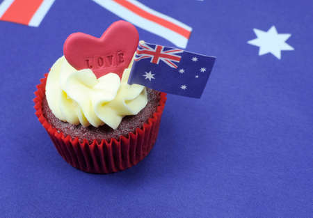 red velvet cupcake: I Love Australia cupcake with love heart and Australian Flag for Australia Day or Anzac Day holidays, against an Australian flag background, with copy space. Stock Photo