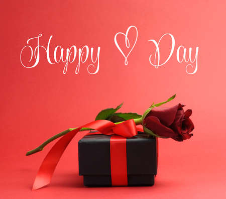 Happy Heart Day, with love heart symbol, greeting with red rose and black jewelry box gift against red background for Valentines Day, or birthday present. photo