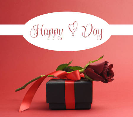 Happy Heart Day, with love heart symbol, Vintage style greeting with red rose and black jewelry box gift against red background for Valentines Day, or birthday present. photo