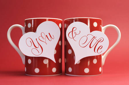 You and Me, love message greeting on heart gift tags on red polka dot coffee mugs for Valentines Day, Mothers Day, birthday, wedding or loving occasion. photo