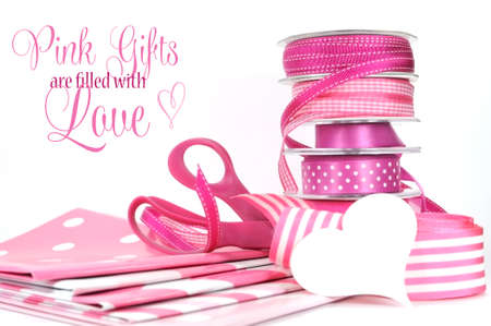 Pink Gifts are filled with Love, greeting with polka dot and plain ribbons, scissors, and wrapping paper for Valentines Day, Mothers Day, birthdays, wedding or Christmas gift wrapping. photo