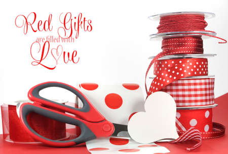 Red Gifts are filled with Love, greeting with polka dot and plain ribbons, scissors, and wrapping paper for Valentines Day, Mothers Day, birthdays, wedding or Christmas gift wrapping. photo