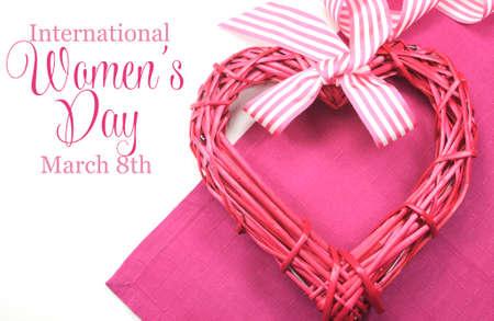 Feliz Día Internacional de la Mujer, 8 de marzo de mensaje de saludo de celebración con corazón de caña de ratán de color rosa y la cinta de la raya