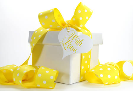 Beautiful pink and white gift box present for christmas valentine yellow theme gift box with yellow polka dot ribbon and white copy space for easter negle Choice Image