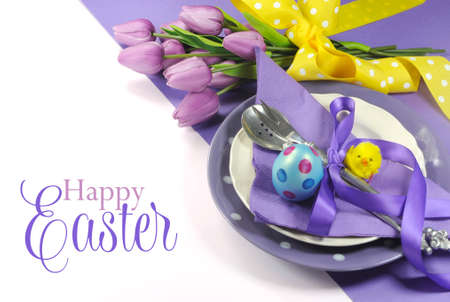sunday: Happy Easter yellow and purple mauve lilac theme easter table place setting, with sample greeting or copy space for your text here