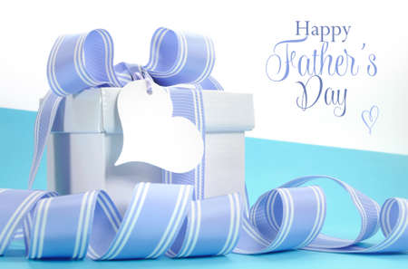 Blue Fathers Day gift with beautiful stripe ribbon and heart shape gift tag and Happy Fathers Day sample text or copy space for your text here.