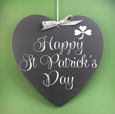 st  patricks: Happy St Patricks Day greeting message with shamrock or copy space on heart shaped blackboard against a green background. Stock Photo