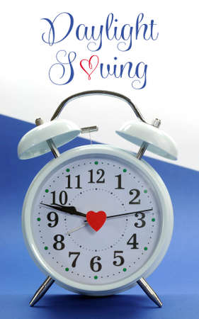 Retro vintage style white alarm clock on blue and white background with Daylight Saving sample text or copy space. photo