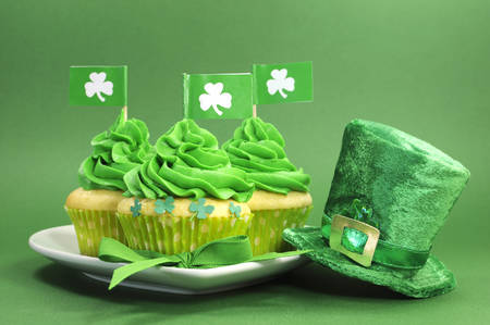 Happy St Patricks Day green cupcakes with shamrock flags and leprechaun hat against a green background photo
