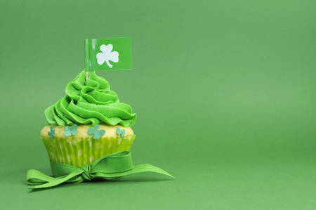 Happy St Patricks Day green cupcake with shamrock flag on green background with copy space for your text here. photo