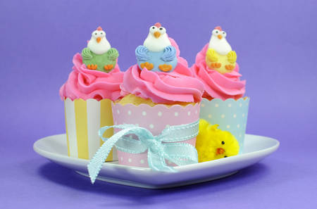 children party: Happy Easter pink, yellow and blue cupcakes with cute chicken decorations on purple background for children party or holiday treat. Stock Photo