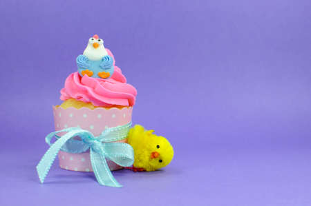 children party: Happy Easter pink, yellow and blue cupcakes with cute chicken decorations on purple background for children party or holiday treat, with copy space.