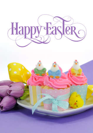 Happy Easter pink, yellow and blue cupcakes with cute chicken decorations and tulips on purple background for children party or holiday treat, with beautiful sample text or copy space for your text here. photo