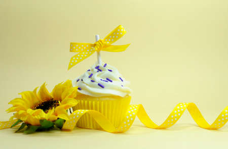 Yellow theme cupcake with sunflower for birthday, mothers day, Easter, bridal or baby shower with copy space for text here. photo