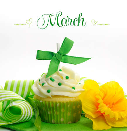 Beautiful green and yellow Spring theme cupcake with daffodils and decorations for the month of March with sample text or copy space for your text here  photo