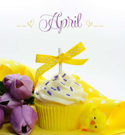 Beautiful yellow Spring or Easter theme cupcake with seasonal flowers tulips and decorations for the month of April with sample text or copy space for your text here