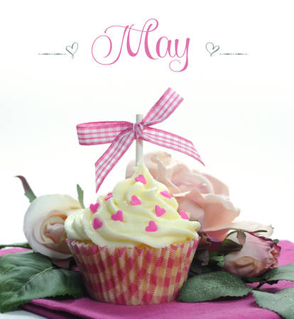 Beautiful pink heart or Mothers Day theme cupcake with seasonal flowers and decorations for the month of May with sample text or copy space for your text here  photo